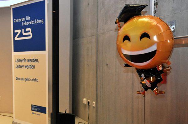 Ein Luftballon in Form eines lachenden Emojis mit Doktorhut