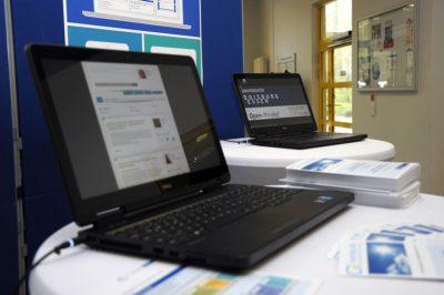 Zwei Laptops vor einer Posterpräsentation