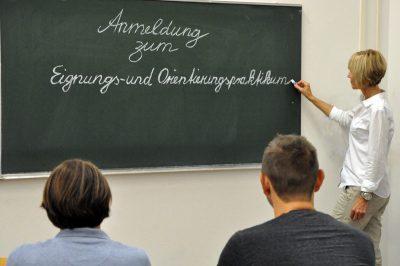 Frau schreibt Schriftzug an Tafel, Studierende im Vordergrund