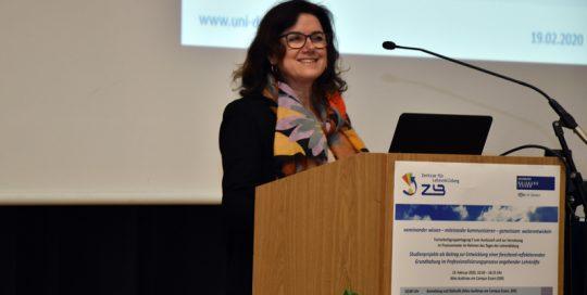 Professorin Dr. Ulrike Weyland steht am Podium und lächelt