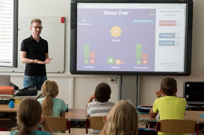 Ein junger Mann steht an einem Smart Board vor einer Schulklasse