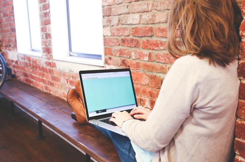 Eine junge Frau sitzt auf einer Bank vor einer Steinwand, mit einem Laptop auf dem Schoß.