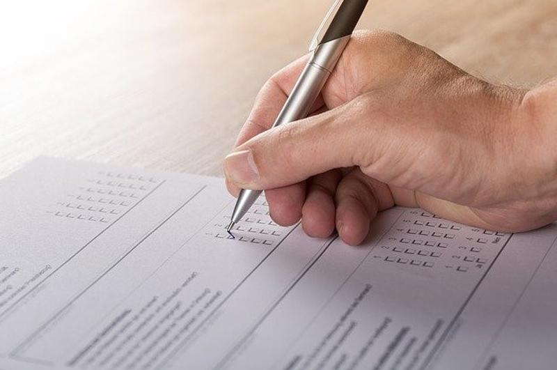Eine Hand hält einen Stift und füllt einen Fragebogen aus