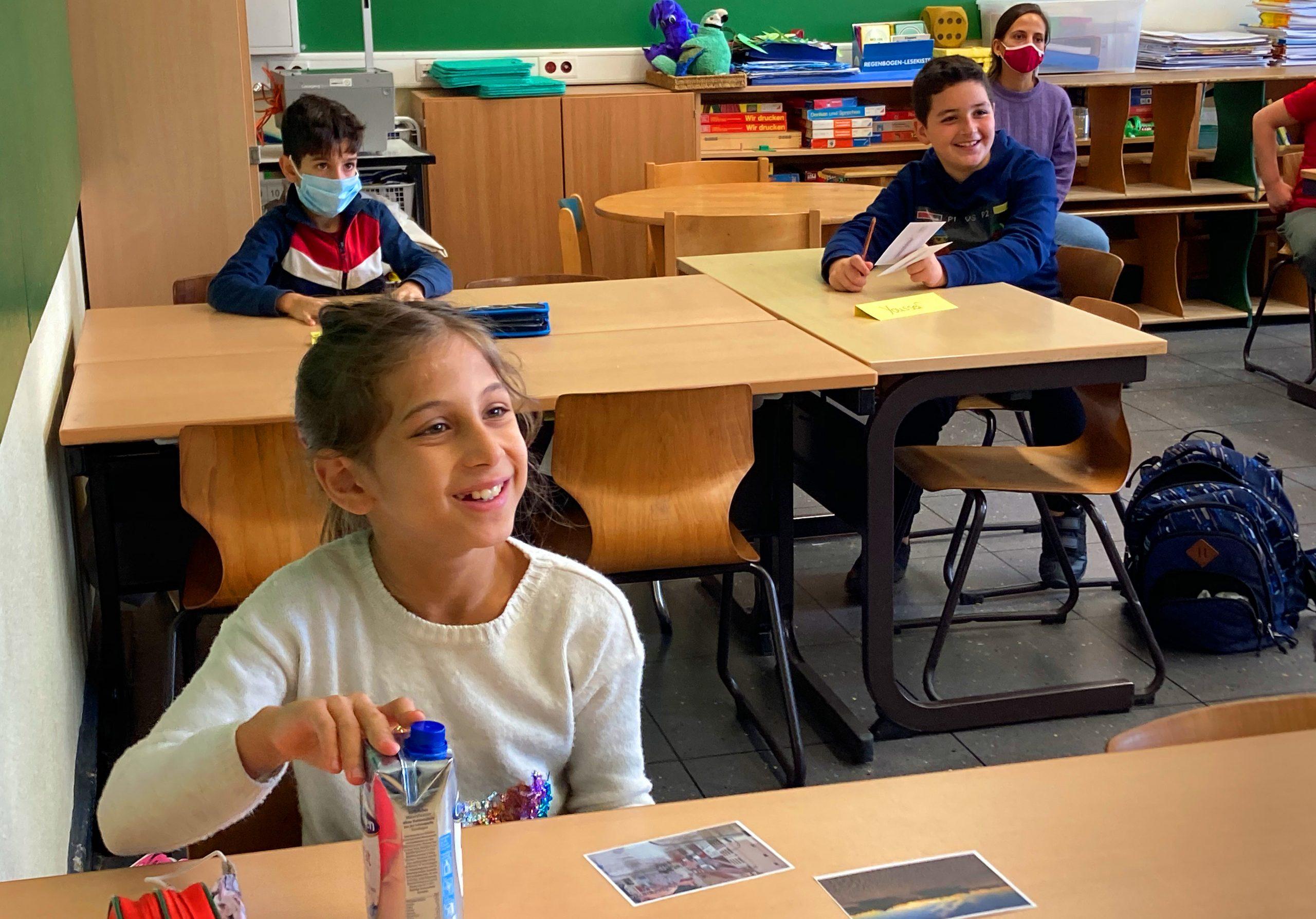 Mehrere Kinder sitzen an Tischen im Klassenzimmer