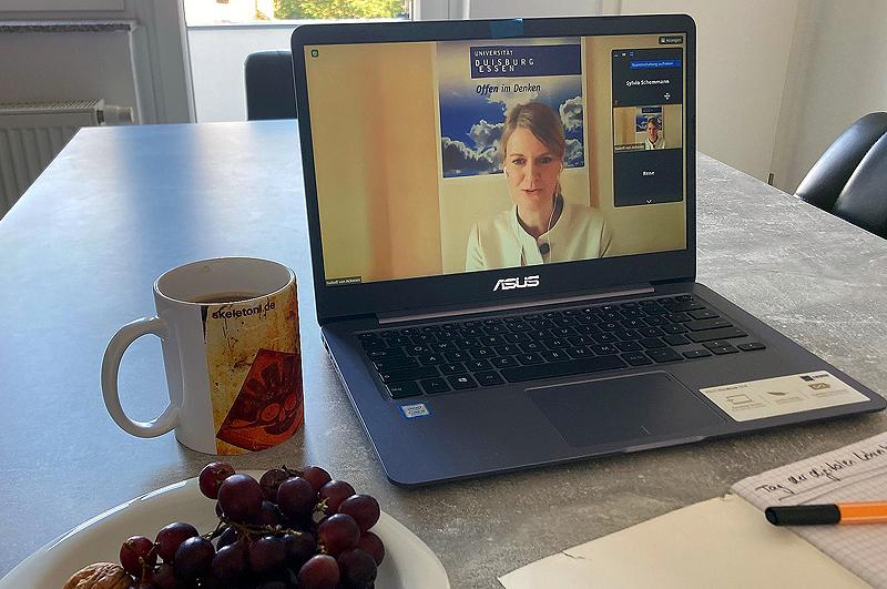 Ein Laptop steht auf dem Tisch, auf dem Bildschirm zu sehen ist Professorin Dr. Isabell van Ackeren während der Veranstaltung