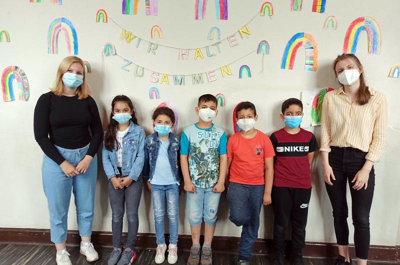 """Zwei junge Frauen und fünf Kinder mit Mund-Nasen-Schutz stehen vor einer Wand mit gemalten Regenbögen und dem Schriftzug """"Wir halten zusammen""""."""