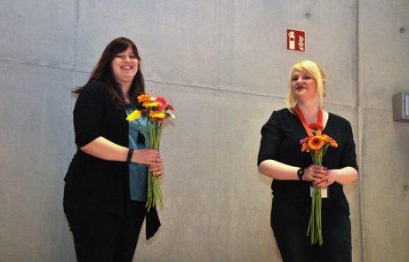 Studentische Hilfskräfte verteilen Blumen an der Abschlussfeier im April 2018