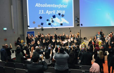 Absolventinnen und Absolventen bei der Abschlussfeier im April 2018 werfen ihre Hüte in die Luft