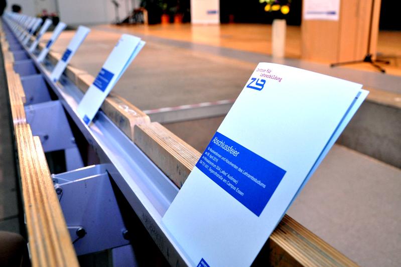 Programme in der Sitzreihe bei der Abschlussfeier